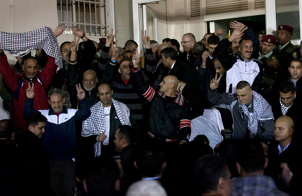 . Released Palestinian prisoners gesture during their welcome ceremony after arriving at the Palestinian headquarters, in the West Bank city of Ramallah, Tuesday, Dec. 31, 2013. Israel released more than two dozen Palestinian prisoners convicted in deadly attacks against Israelis early Tuesday as part of a U.S.-brokered package to restart Mideast peace talks. (AP Photo/Nasser Nasser)