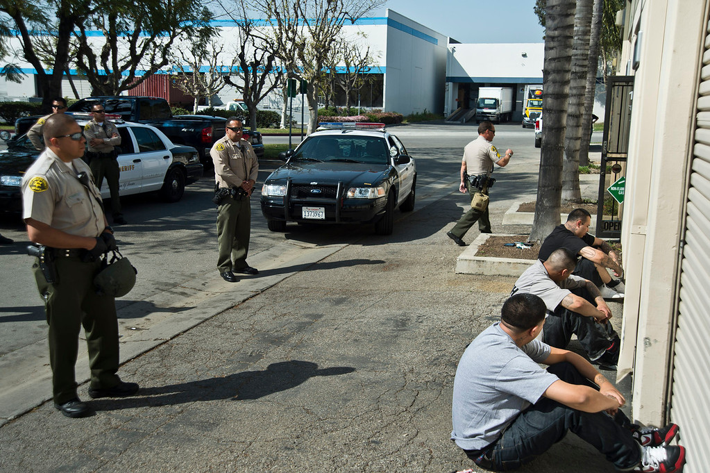. Los Angeles County Sheriff\'s deputies detain three employees as federal Food and Drug Administration officers serve a search warrant to auto parts dealer, L.A. Rush, in Norwalk on Friday, March 22, 2013. The business is suspected of illegally selling nitrous oxide for recreational drug use. (SGVN/Staff photo by Watchara Phomicinda)
