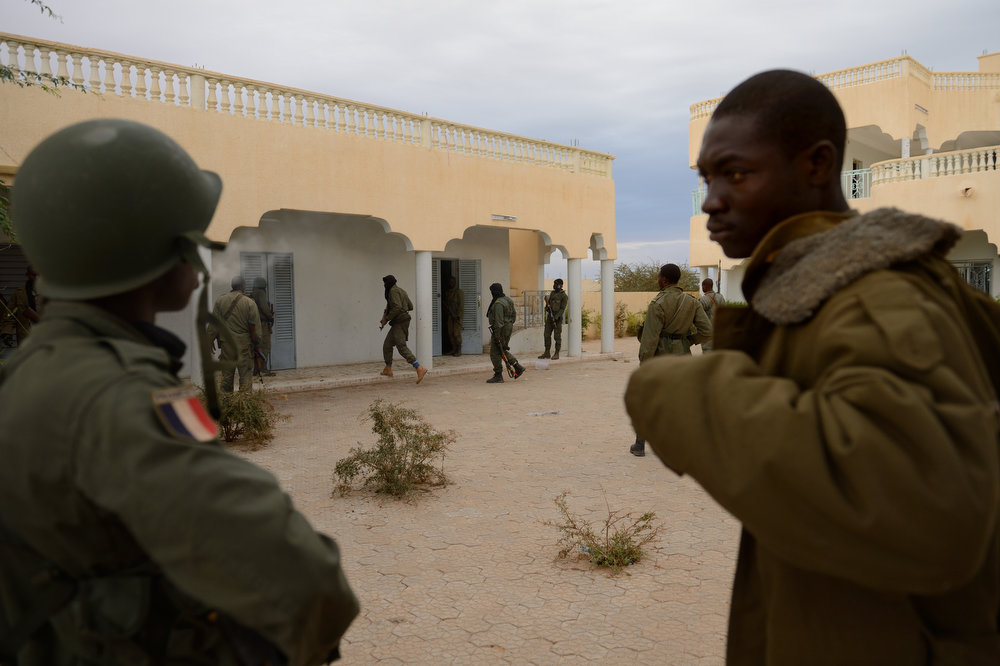 Description of . A Malian soldier with a French flag insignia watches soldiers entering a house which was held by Islamists after Malian and French soldiers entered the historic city of Timbuktu, occupied for 10 months by Islamists who imposed a harsh form of sharia, on January 28, 2013. Residents of the ancient city on the edge of the Sahara desert erupted in joy as the French-led troops entered the town, jubilantly waving French and Malian flags after months of suffering under the Islamists\' brutal rule.   ERIC FEFERBERG/AFP/Getty Images