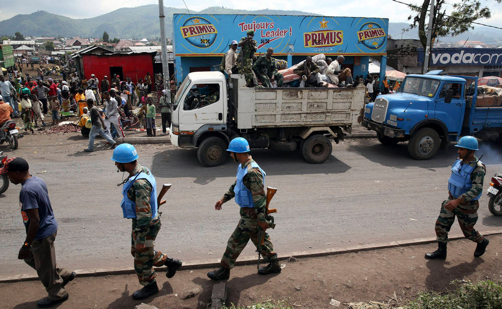 Description of . United Nations (U.N.) soldiers pass M-23 rebel fighters in a truck, as the rebels withdraw from Goma December 1, 2012. Rebel fighters, singing and brandishing weapons, pulled out of Democratic Republic of Congo's eastern border city of Goma on Saturday, raising hopes regional peace efforts could advance negotiations to end the insurgency.    REUTERS/Goran Tomasevic