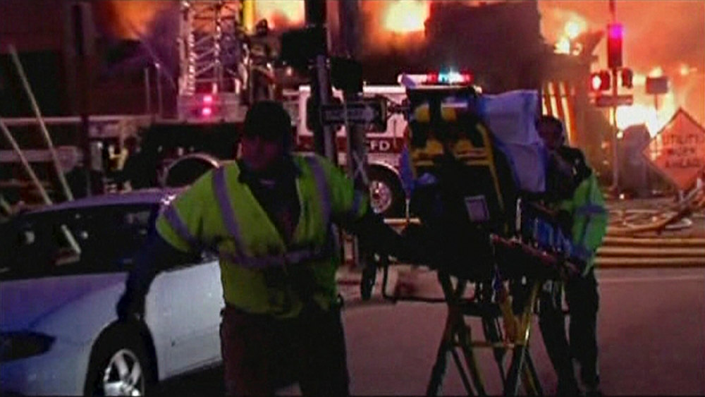 Description of . A still image taken from a KHSB-TV video footage shows emergency workers pulling a person on a gurney near the scene of the fire at Kansas City, Missouri February 19, 2013. A fire triggered by a natural gas explosion that appeared to have originated underground engulfed a restaurant in Kansas City, Missouri, on Tuesday, injuring more than a dozen people, authorities and witnesses said.  REUTERS/KHSB-TV
