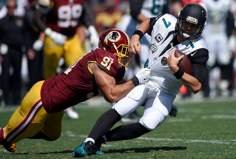. Washington Redskins outside linebacker Ryan Kerrigan (91) pulls down Jacksonville Jaguars quarterback Chad Henne (7) during the first half of an NFL football game Sunday, Sept. 14, 2014, in Landover, Md. (AP Photo/Nick Wass)