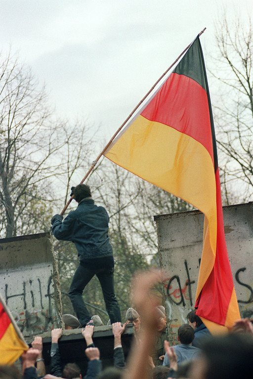 . A West Berliner prepares to hand over a FRG flag to East German Vopos through a portion of the fallen Berlin Wall near the Brandenbourg Gate early 11 November 1989. Two days before, Gunter Schabowski, the East Berlin Communist party boss, declared that starting from midnight, East Germans would be free to leave the country, without permission, at any point along the border, including the crossing-points through the Wall in Berlin.     (Photo credit GERARD MALIE/AFP/Getty Images)