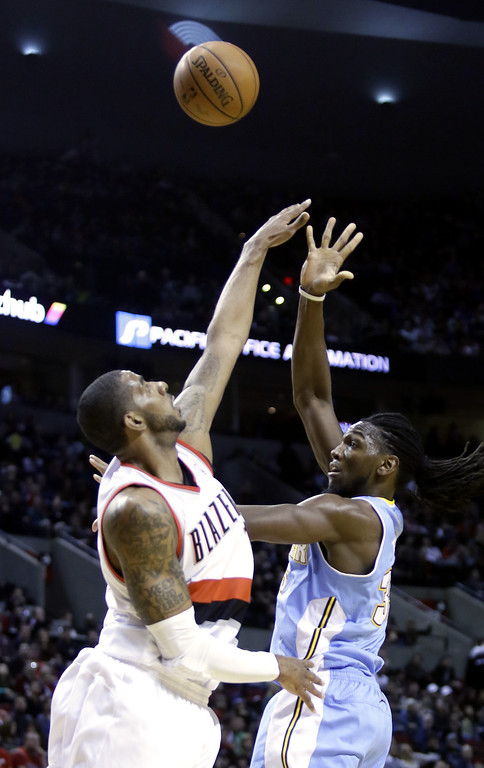 . Denver Nuggets forward Kenneth Faried, right, shoots over Portland Trail Blazers forward LaMarcus Aldridge during the first half of an NBA basketball game in Portland, Ore., Saturday, March 1, 2014. (AP Photo/Don Ryan)