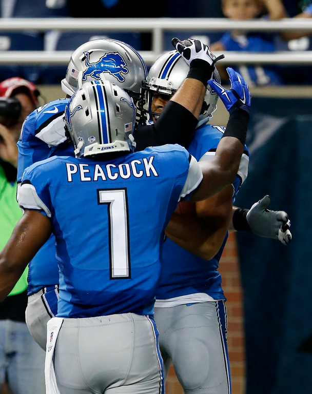 . Detroit Lions wide receiver Corey Fuller, right, celebrates his 21 yard touchdown catch with Andrew Peacock (1) and a another teammate during the fourth quarter of a preseason NFL football game against the Detroit Lions at Ford Field Saturday, Aug. 9, 2014, in Detroit. The Lions defeated the Browns 13-12. (AP Photo/Duane Burleson)