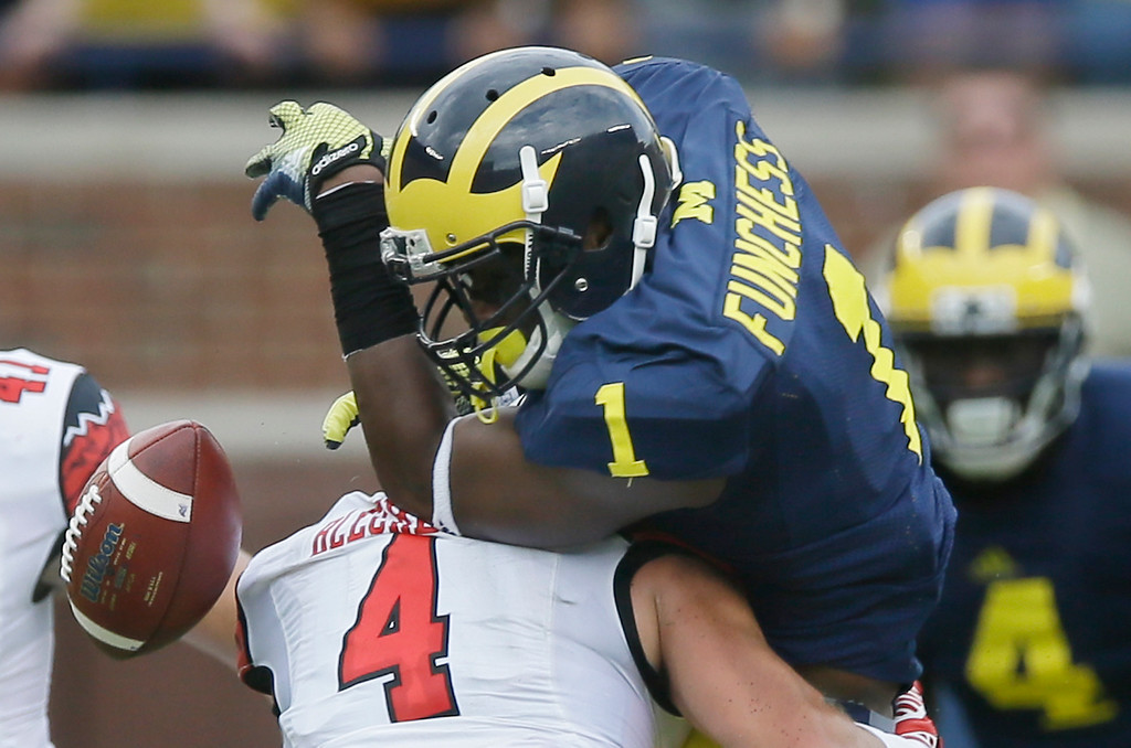 . Utah defensive back Brian Blechen (4) knocks the ball away from Michigan wide receiver Devin Funchess (1) during the first half of an NCAA college football game in Ann Arbor, Mich., Saturday, Sept. 20, 2014.  (AP Photo/Carlos Osorio)