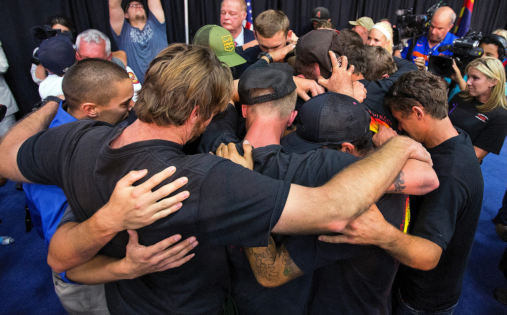 . Firefighters gather in an embrace to a standing ovation during a memorial service on Monday, July 1, 2013, for the 19 firefighters of the Granite Mountain Hotshot Crew that were killed battling a wildfire on Sunday in Prescott, Ariz. (AP Photo/The Arizona Republic, Tom Tingle)