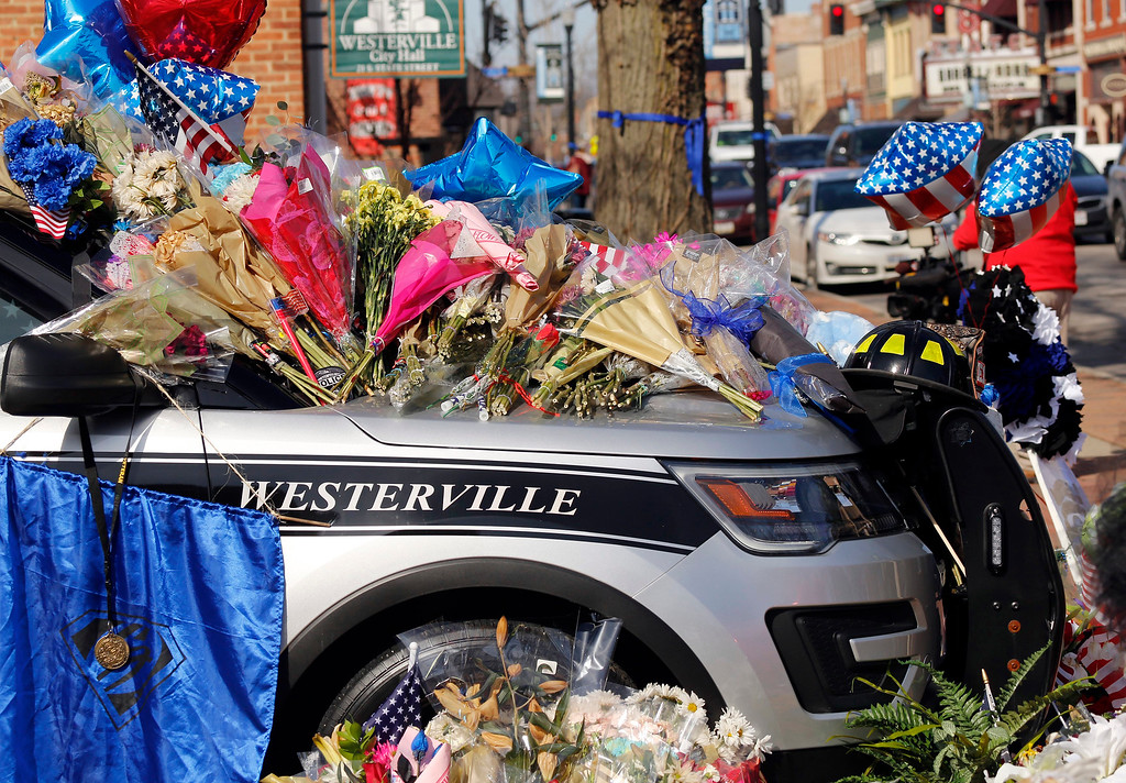 . Flowers and signs adorn a Westerville Police car at a memorial outside the police department following a procession transporting the bodies of Westerville Police Officer Eric Joering and Anthony Morelli from the Franklin County Coroners Office to the Hill and Moreland funeral homes in Westerville, Ohio, Monday, Feb. 12, 2018. (Adam Cairns/The Columbus Dispatch via AP)