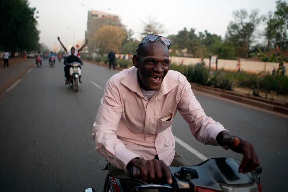 . Malians celebrate on their motorcycles a visit by France\'s President Francois Hollande in Bamako, Mali February 2, 2013. France will withdraw its troops from Mali once the Sahel state has restored sovereignty over its national territory and a U.N.-backed African military force can take over from the French soldiers, Hollande said on Saturday. REUTERS/Joe Penney