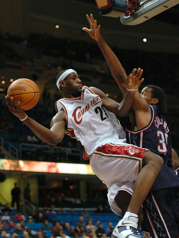 . Michael Blair/News-Herald The Cavs\' LeBron James looks for an open man as he gets pressured under the basket by Nets center Jason Collins during the first half of Monday night\'s game at Gund Arena.