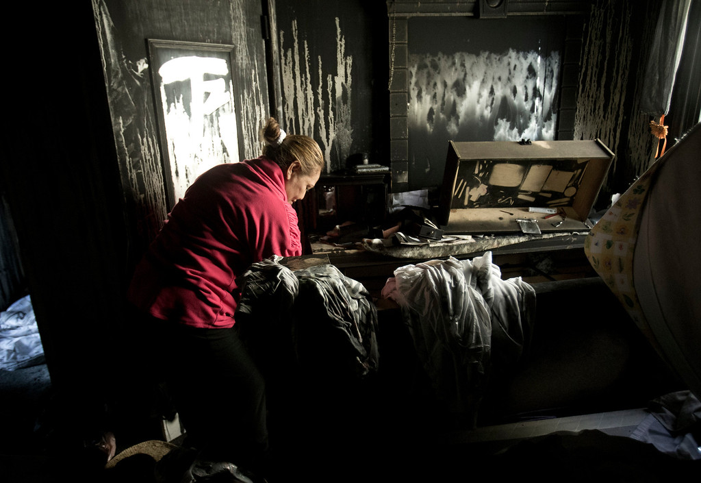 . Anna Paasi searches for salvageable possessions in the bedroom of their house that was destroyed by a fire in December, in San Mateo, Calif. on Thursday, Jan. 2, 2014.  (LiPo Ching/Bay Area News Group)