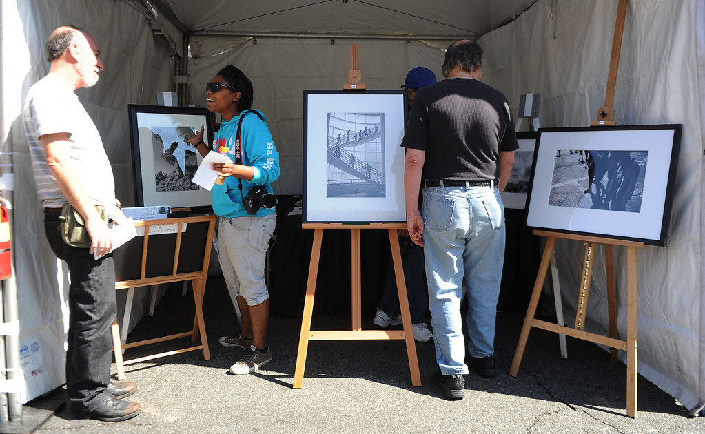 . Locals look over the photography of David Behar during the 8th Annual Pasadena ARTWalk along El Molino Avenue between Colorado Boulevard and Green Street in Pasadena, Calif., on Saturday, Oct. 12, 2013. The ArtWalk features over 30 participating artists, art sales, gallery walks, musical performances and other activities.   (Keith Birmingham Pasadena Star-News)