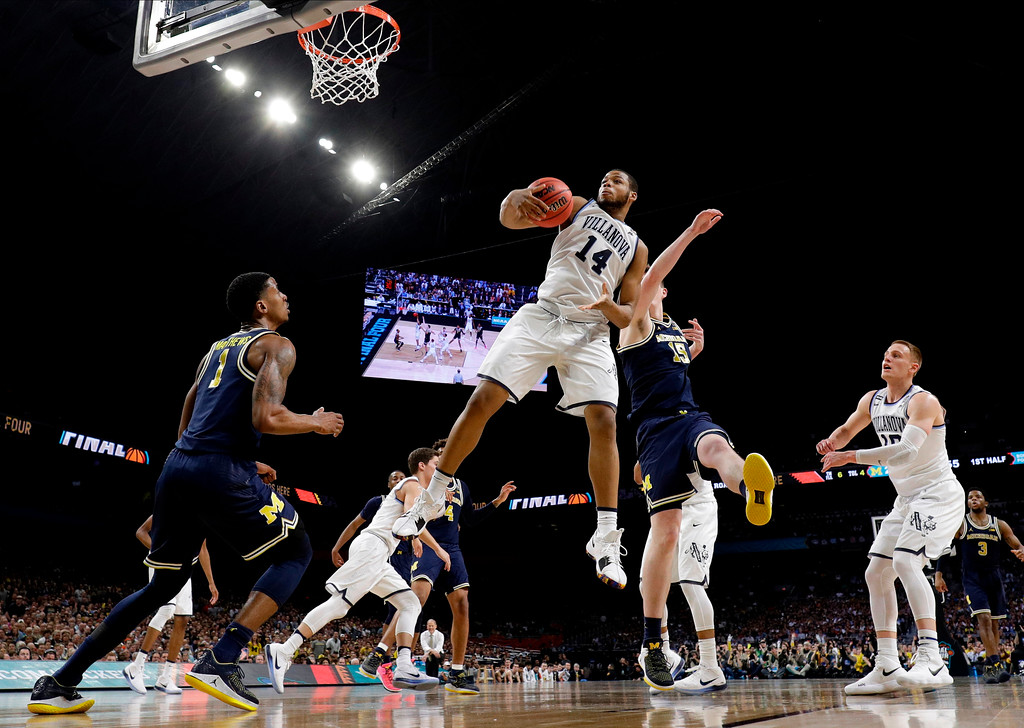 . Villanova forward Omari Spellman (14) grabs a rebound in front of Michigan center Jon Teske during the first half in the championship game of the Final Four NCAA college basketball tournament, Monday, April 2, 2018, in San Antonio. (AP Photo/David J. Phillip)
