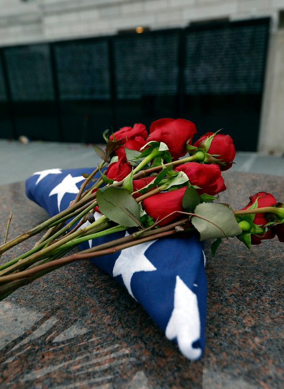 . A folded American flag and roses lay across from the Statewide Fallen Officers memorial during the Mississippi Law Enforcement Memorial Candlelight Vigil in Jackson, Miss., Tuesday, May 15, 2018. (AP Photo/Rogelio V. Solis)