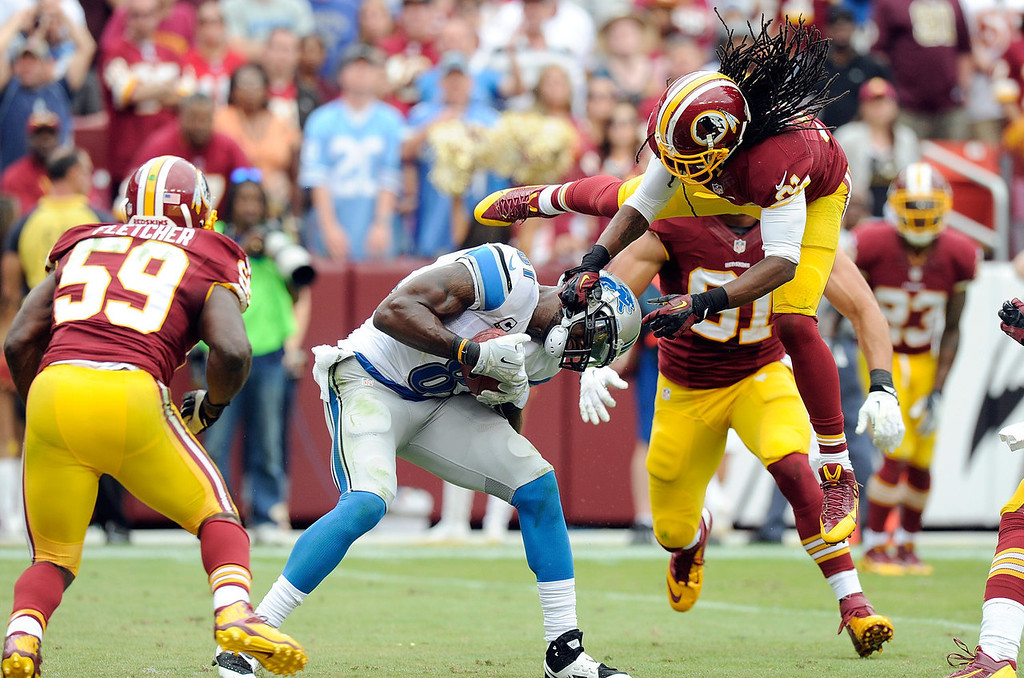 . Calvin Johnson #81 of the Detroit Lions breaks a tackle by Brandon Meriweather #31 of the Washington Redskins and scores a touchdown in the fourth quarter at FedExField on September 22, 2013 in Landover, Maryland. Detroit won the game 27-20. (Photo by Greg Fiume/Getty Images)