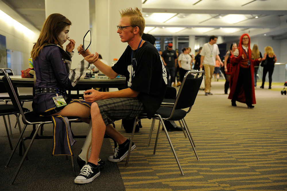 . Jeanette Trytek dressed as Mad Moxxi touches up her make up as Gage Hillis holds a mirror up for her during Denver Comic Con at the Colorado Convention Center on June 2, 2013 in Denver, Colorado. (Photo by Seth McConnell/The Denver Post)