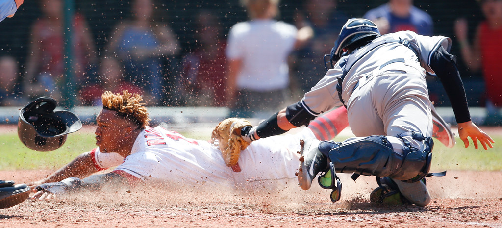 . Cleveland Indians\' Jose Ramirez scores past New York Yankees\' Kyle Higashioka on a sacrifice fly by Yan Gomes during the eighth inning of a baseball game, Sunday, July 15, 2018, in Cleveland. The Indians defeated the Yankees 5-2. (AP Photo/Ron Schwane)