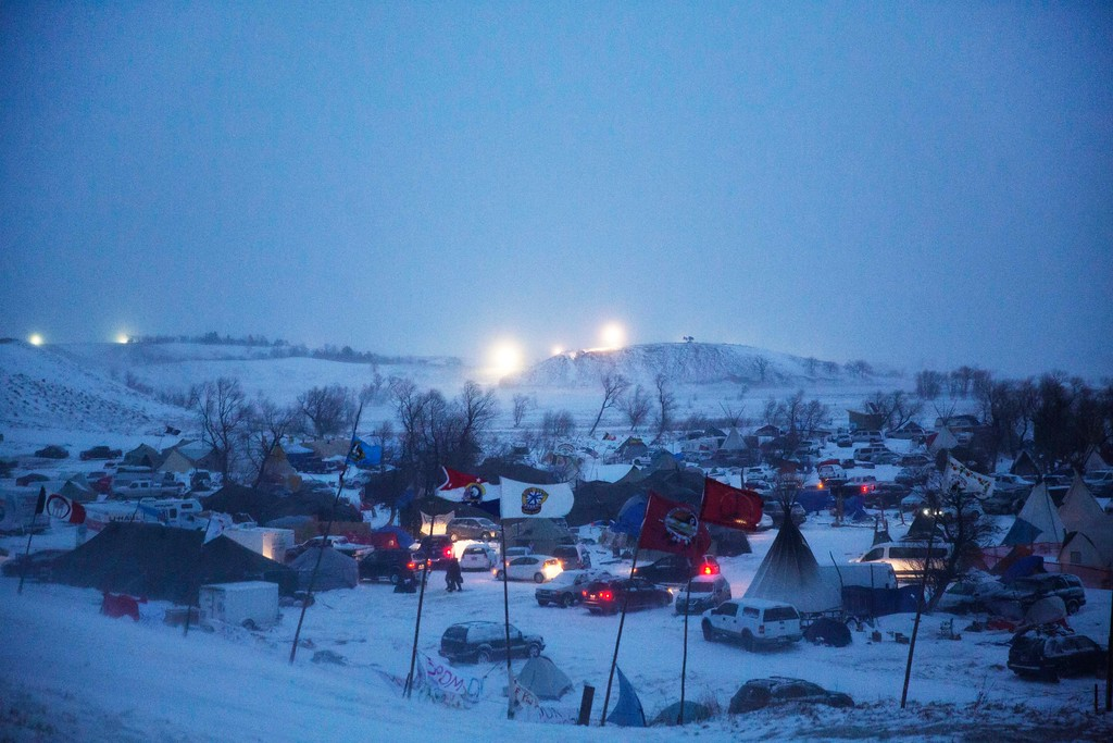 . Lights from the Dakota Access oil pipeline site are seen on the horizon overlooking the Oceti Sakowin camp where people have gathered to protest the Dakota Access oil pipeline is seen in a snow storm in Cannon Ball, N.D., Tuesday, Dec. 6, 2016. An overnight storm brought several inches of snow, winds gusting to 50 mph and temperatures that felt as cold as 10 degrees below zero. (AP Photo/David Goldman)