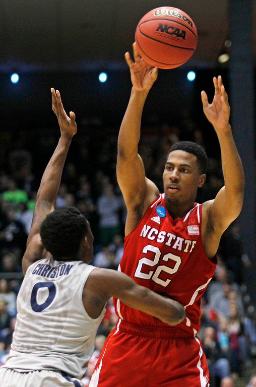 . North Carolina State guard Ralston Turner (22) passes over Xavier guard Semaj Christon during the first half of a first-round game of the NCAA college basketball tournament, Tuesday, March 18, 2014, in Dayton, Ohio. (AP Photo/Skip Peterson)