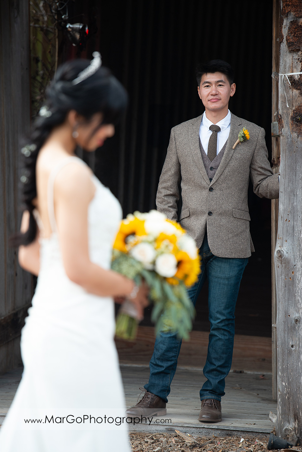 portrait of the groom with bride holding yellow flower bouquet in foreground at Long Branch Saloon & Farms in Half Moon Bay