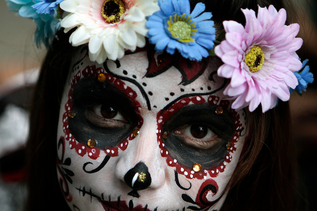 ". Girl scout Montso Gomez, 12, dressed as a ""Catrina,\"" or skeleton lady, waits for the start of the Gran Procession of the Catrinas, to mark the upcoming Day of the Dead holiday, in Mexico City, Sunday, Oct. 23 2016. The gran procession is one of many that will take place in Mexico City as part of the celebrations, culminating with visits to the graves of departed loved ones on Nov. 1 and 2. The figure of a skeleton wearing broad-brimmed hat was first done as a satirical engraving by artist Jose Guadalupe Posada sometime between 1910 and his death in 1913, to poke fun at women who pretended to be European by dressing elegantly and as a critique of social stratification. (AP Photo/Anita Baca)"