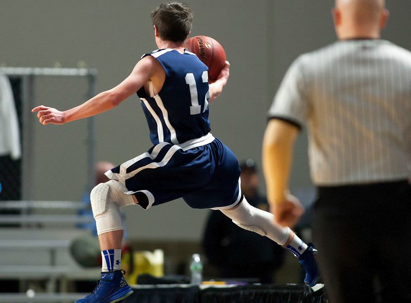 BANGOR, Maine -- 03/04/2017 -- Greenville's Noah Pratt leaps in the air to save the ball from going out of bounds against Machias during their Class D boys basketball state championship at the Cross Insurance Center in Bangor Saturday. Ashley L. Conti   BDN