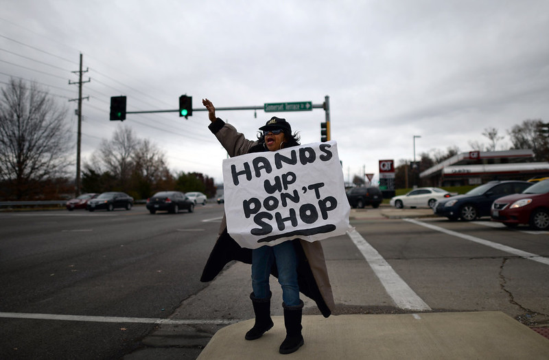 . A woman urges people not to shop as she protests the death of 18-year-old Michael Brown in Ferguson, Missouri, on November 22, 2014. Tensions rose on November 22 in the troubled St Louis suburb of Ferguson, with a grand jury poised to decide whether to prosecute a white police officer for killing an unarmed black teenager. US President Barack Obama has called for calm, Missouri\'s governor declared a state of emergency and activated the state National Guard, and the FBI has deployed an extra 100 personnel in the city.Police helicopters trained search lights over Ferguson late Friday as a small gaggle of protesters braved the cold to demand that officer Darren Wilson stand trial for shooting 18-year-old Michael Brown on August 9. JEWEL SAMAD/AFP/Getty Images
