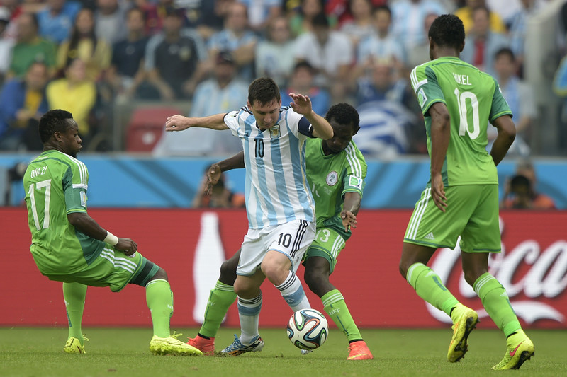 . Nigeria\'s midfielder Ogenyi Onazi (L), defender Juwon Oshaniwa (2nd R) and midfielder John Obi Mikel (R) vie for the ball with Argentina\'s forward Lionel Messi, during a Group F football match between Nigeria and Argentina at the Beira-Rio Stadium in Porto Alegre during the 2014 FIFA World Cup on June 25, 2014.  (JUAN MABROMATA/AFP/Getty Images)