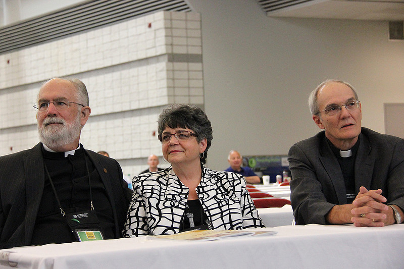 The Rev. Wm. Chris Boerger, his wife and the Rev. Michael Cooper-White wait for the announcement of the secretary election.