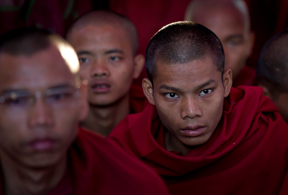 Description of . A young Buddhist monk watches protesters at a meeting during an occupy of the office entrance to the Chinese copper mine company Wan Bao Co. Ltd in Letpadaung mine, Monywa township, northwestern Myanmar, Wednesday, Nov 28, 2012. Hundreds of Buddhist monks and villagers occupying a Letpadaung mine defied a government order to leave by Wednesday, saying they will stay until the project is halted. The protest is the latest example of increased activism by citizens since an elected government took over last year following almost five decades of repressive military rule. (AP Photo/Gemunu Amarasinghe)