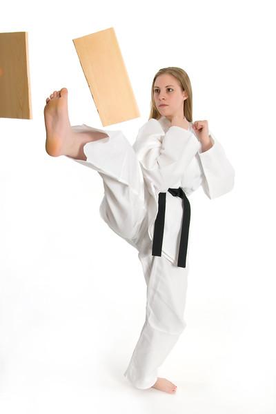 Black belt female martial artist doing board break.