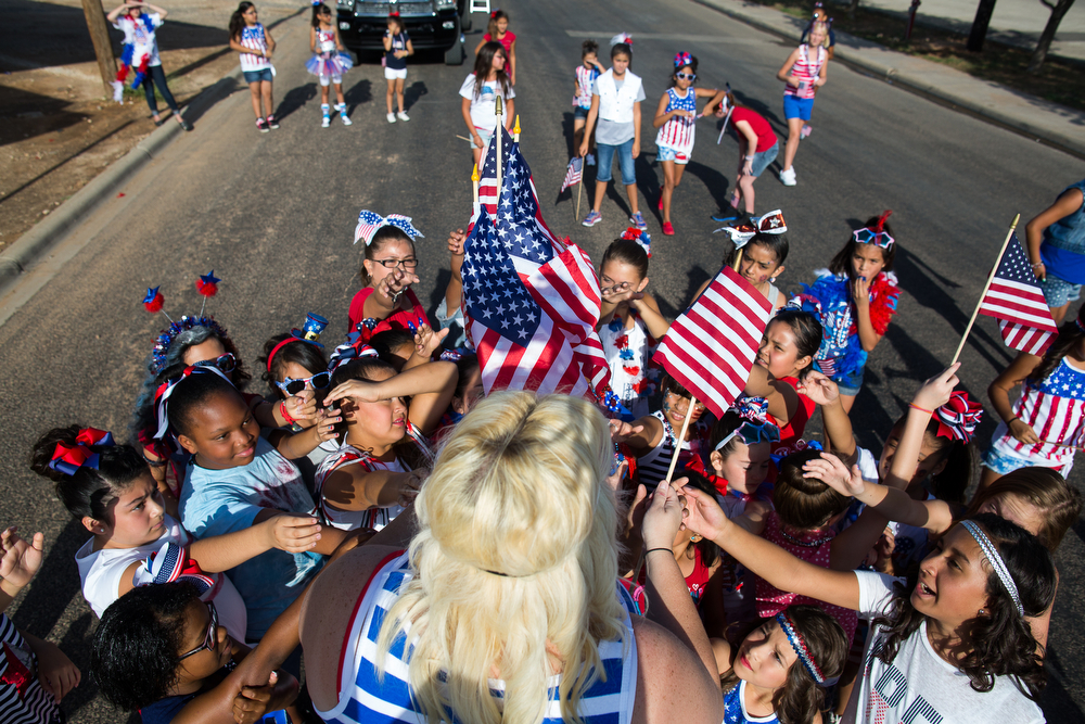 Description of . Elasha Ramirez hands out American flags before the 65th annual Jaycees Independence Day parade, Friday, July 4, 2014, in Odessa, Texas. (AP Photo/The Odessa American, Courtney Sacco)