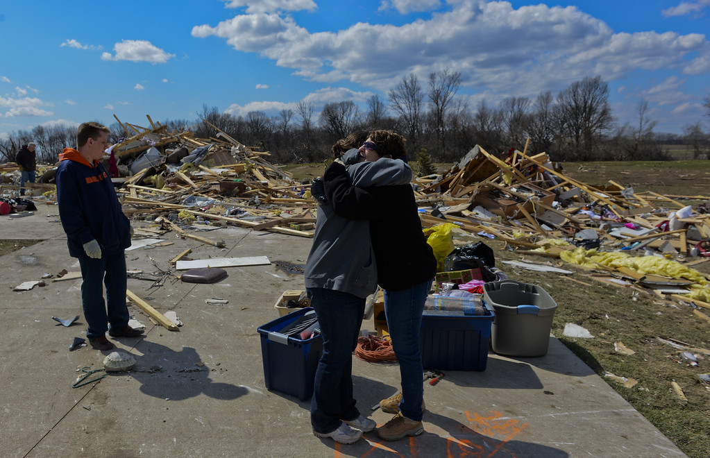 . John Whitaker, left, looks on as Jean Van Hise and Mary Kay Merema hug outside his destroyed home in the Cherry Hill subdivision outside of Flagg Center, Ill., on Friday, April 10, 2015.   The National Weather Service says at least two tornadoes churned through six north-central Illinois counties. (AP Photo/Matt Marton)