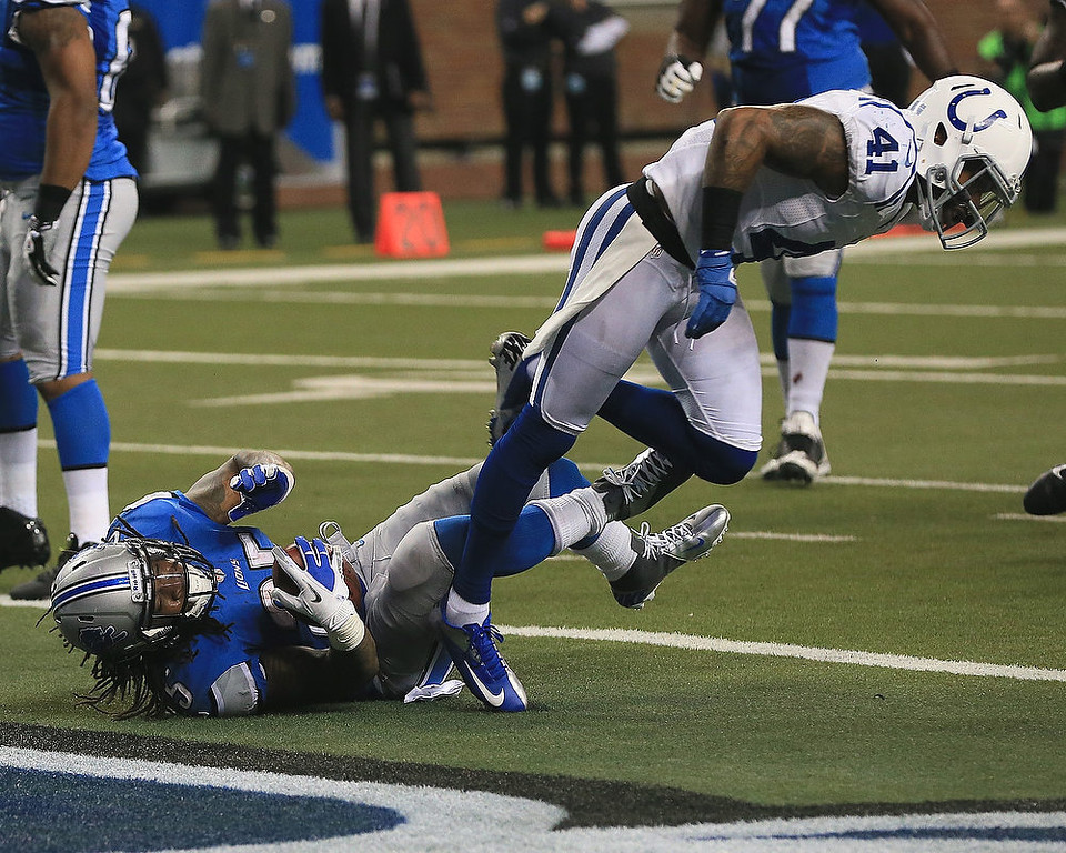 . Mikel Leshoure #25 of the Detroit Lions dives in the end zone for a touchdown under Antoine Bethea #41 of the Indianapolis Colts at Ford Field on December 2, 2012 in Detroit, Michigan.  (Photo by Dave Reginek/Getty Images)