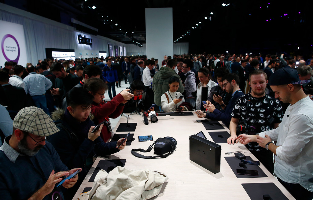 . People attend the Samsung Galaxy Unpacked 2018 event on the eve of the Mobile World Congress wireless show, in Barcelona, Spain, Sunday, Feb. 25, 2018. Samsung unveiled new smartphones with largely unchanged designs and incremental improvements such as a better camera. (AP Photo/Manu Fernandez)