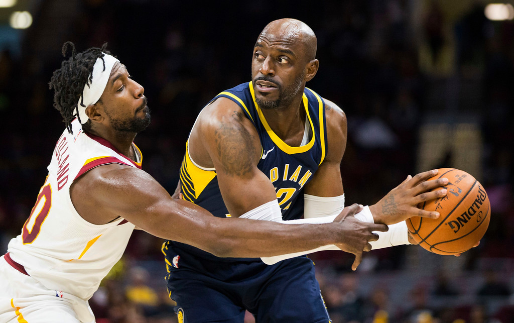 . Cleveland Cavaliers\' John Holland, left, reaches for the ball against Indiana Pacers\' Damien Wilkins during the fourth quarter of an NBA preseason basketball game, Friday, Oct. 6, 2017, in Cleveland. The Pacers won 106-102. (AP Photo/Scott R. Galvin)