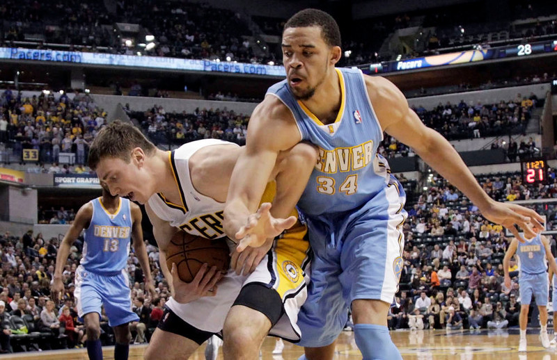 . Indiana Pacers forward Tyler Hansbrough, left, tries to keep the ball away from Denver Nuggets center JaVale McGee on an inbounds play during the first half of an NBA basketball game in Indianapolis, Friday, Dec. 7, 2012. (AP Photo/AJ Mast)