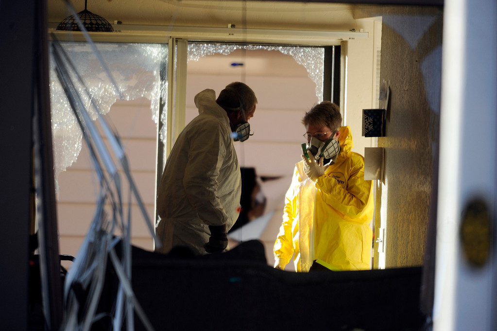 . Investigators enter a town home at 16005 Ithaca Place in Aurora Saturday afternoon. The bodies of four people, including a gunman are dead at the scene following a standoff situation early Saturday morning. The Denver Post/ Karl Gehring