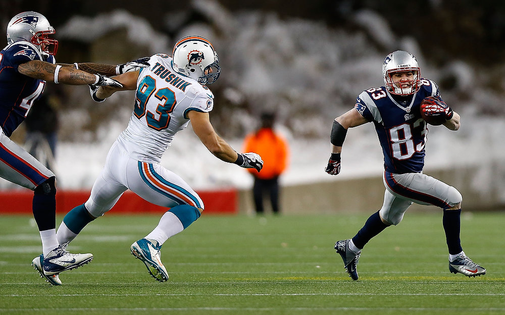 . Wes Welker #83 of the New England Patriots runs with the ball after catching a pass in front of Jason Trusnik #93 of the Miami Dolphins during the game at Gillette Stadium on December 30, 2012 in Foxboro, Massachusetts. (Photo by Jared Wickerham/Getty Images)