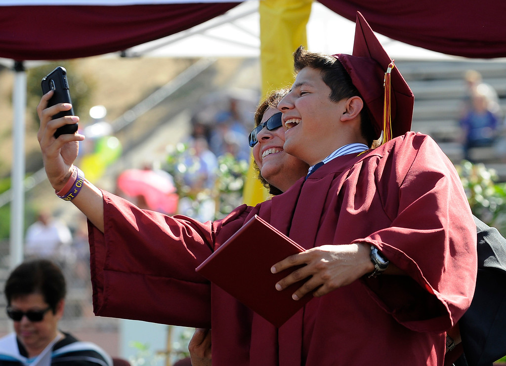 . After getting his diploma, Miguel Figueroa takes a self portrait of himself with Religion and Ethics teacher,  Jan Galla. The Commencement Exercises for the Bishop Alemany High School Class of 2013 was held at College of the Canyons in Santa Clarita, CA 6/1/2013(John McCoy/LA Daily News)