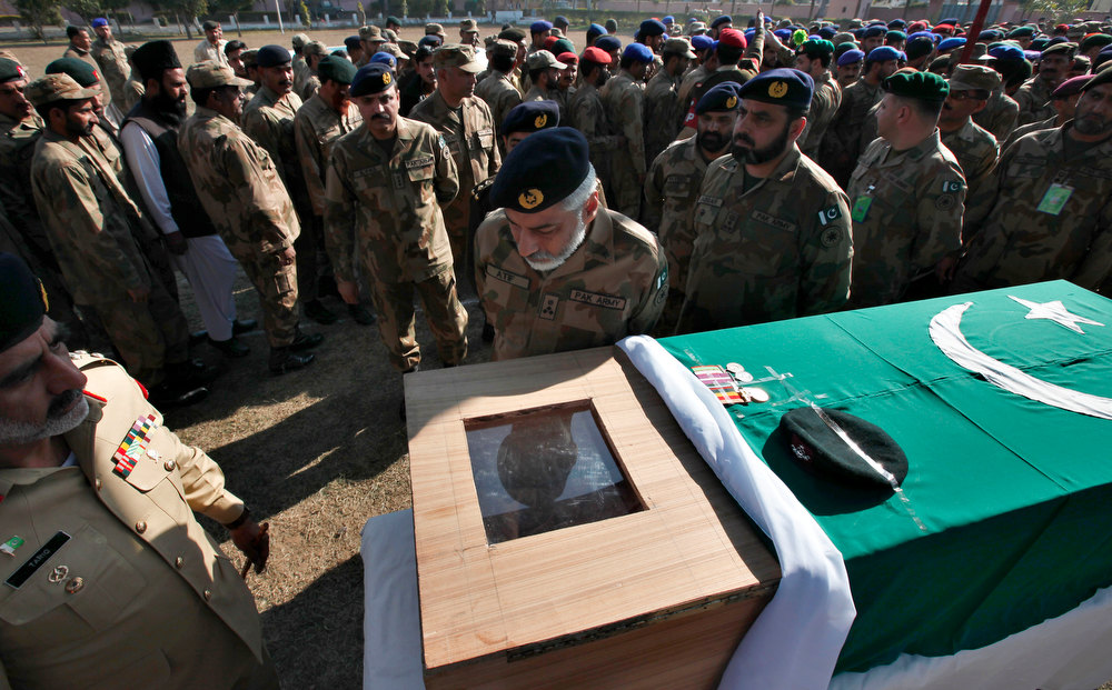 . Pakistani army officers and soldiers gather beside the casket of their colleague, Havildar Mohyuddin, who was killed by Indian troops firing on a post in the disputed Kashmir border, following a funeral prayer in Jhelum, Pakistan on Friday, Jan. 11, 2013. Pakistan has summoned India\'s top diplomat in the country to protest a pair of clashes along the disputed Kashmir border in the past week that killed two Pakistani soldiers. (AP Photo)