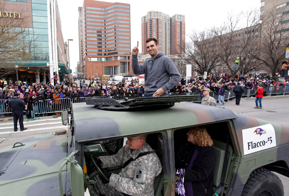 Description of . Baltimore Ravens quarterback and Super Bowl MVP Joe Flacco waves to the crowd gathered on the team's parade route in Baltimore, Maryland February 5, 2013. The Ravens defeated the San Francisco 49ers to win the NFL championship.  REUTERS/Richard Clement