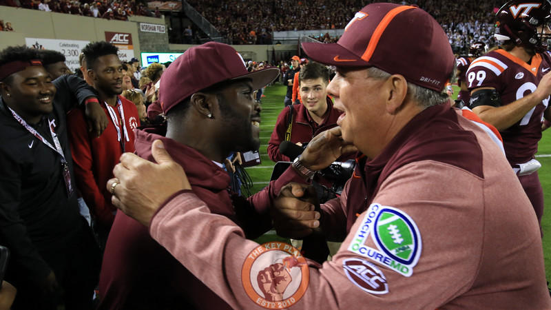 Former Virginia Tech quarterback Michael Vick greets assistant coach Charley Wiles on the sidelines during warmups. (Mark Umansky/TheKeyPlay.com)