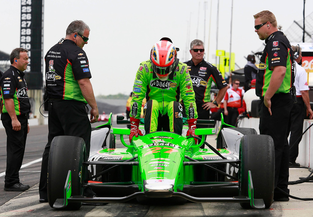 . Andretti Autosport driver James Hinchcliffe of Canada climbs into his race car surrounded by crew members during a practice session at the Indianapolis Motor Speedway in Indianapolis, Indiana May 16, 2013. The 97th running of the Indianapolis 500 is scheduled for May 26.  REUTERS/Brent Smith