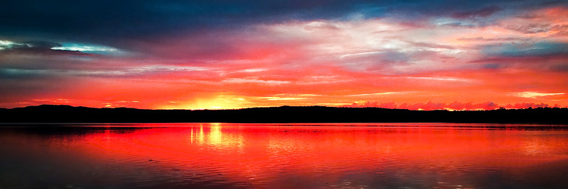Magnificent red cloud coastal sunrise reflections.