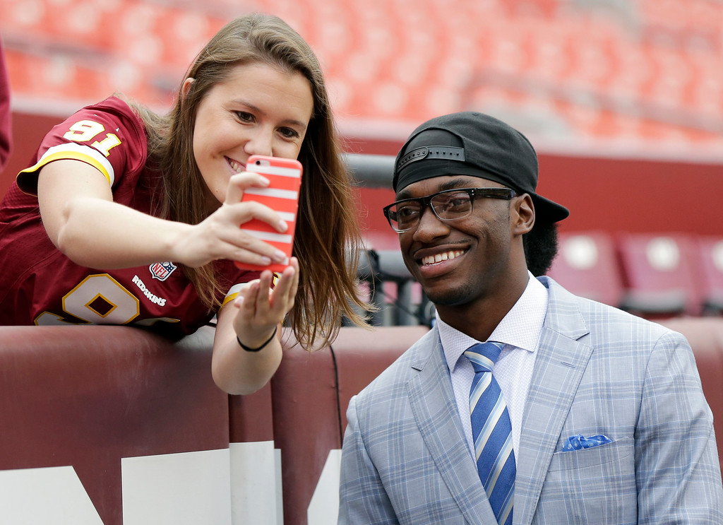 . Injured Cleveland Browns quarterback Robert Griffin III takes a selfie with a Washington Redskins fan before an NFL football game Sunday, Oct. 2, 2016, in Landover, Md. (AP Photo/Mark Tenally)