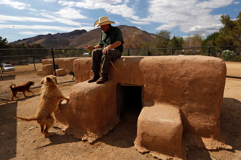. Leo Grillo sita atop one of dozens of dog shelters, made from bales of straw, plywood and stucco, at his DELTA (Dedication & Everlasting Love to Animals) Rescue complex in Acton, Calif. Aug. 29, 2013. (AP Photo/Reed Saxon)