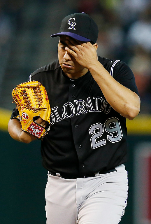 . Colorado Rockies pitcher Jorge De La Rosa wipes sweat from his face during the seventh inning of a baseball game against the Arizona Diamondbacks Sunday, Aug. 31, 2014, in Phoenix.  De La Rosa was pulled from the game in the seventh inning after giving up a two-run home run to Arizona Diamondbacks pinch hitter Nolan Reimold. (AP Photo/Ross D. Franklin)