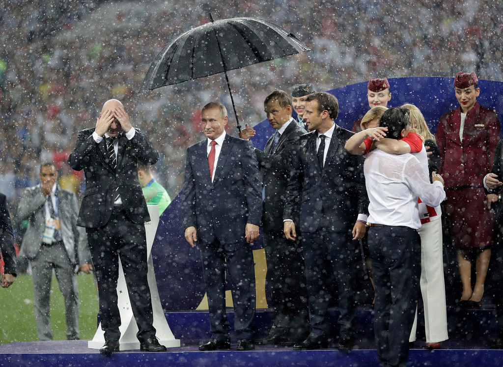 . FIFA President Gianni Infantino, left, wipes rain from his head as Russian President Vladimir Putin stands underneath an umbrella as Croatian President Kolinda Grabar-Kitarovic greets Croatia head coach Zlatko Dalic after the final match between France and Croatia at the 2018 soccer World Cup in the Luzhniki Stadium in Moscow, Russia, Sunday, July 15, 2018. France won the final 4-2. (AP Photo/Matthias Schrader)