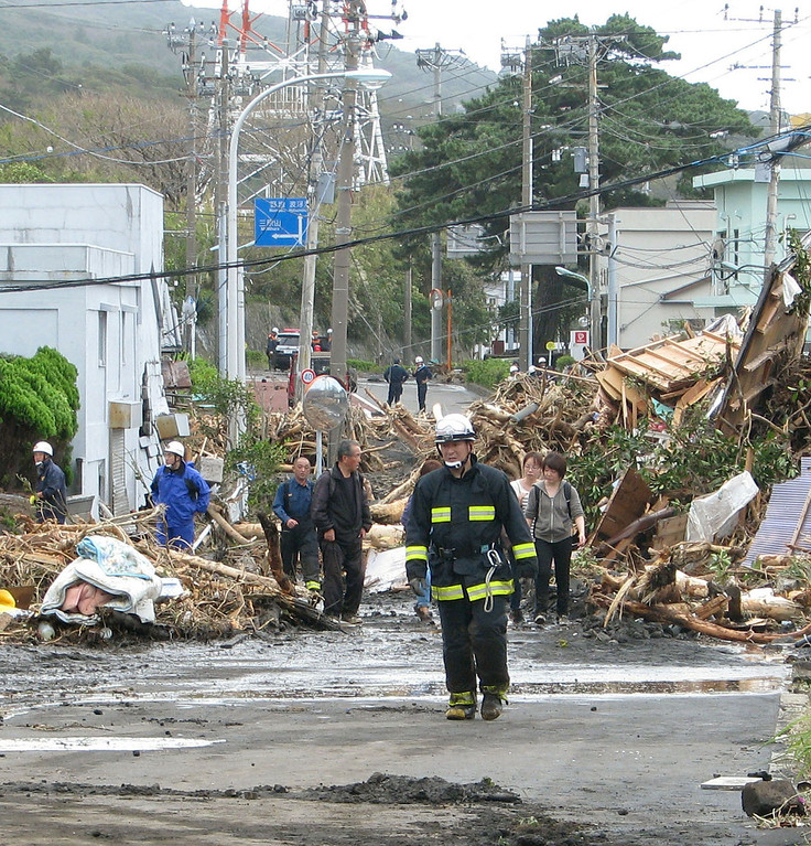 . Rescue workers and residents walk through the rubble of houses in Oshima damaged by landslides after a powerful typhoon hit Izu Oshima island, about 120 kilometers (75 miles) south of Tokyo Wednesday morning, Oct. 16, 2013. (AP Photo/Kyodo News)